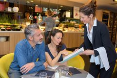 Restaurant waitress giving menu to customers. Restaurant waitress giving the menu to the customers Stock Photos