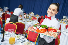 Restaurant waitress serving table with food Stock Image