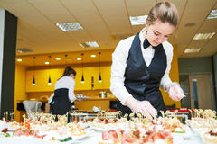 Restaurant waitress serving table with food Royalty Free Stock Photography