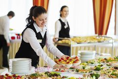 Restaurant waitress serving table with food. The waiters set the tables in the restaurant for the banquet Royalty Free Stock Photos