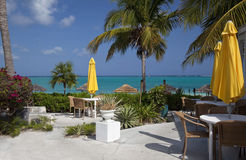 Restaurant by the Water. Tables and yellow umbrellas by the blue-green water of Grace Bay Beach, Providenciales, Turks & Caicos Islands Royalty Free Stock Photography