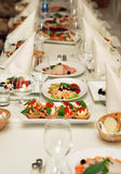 Restaurant wedding banquet table. Table in restaurant with food silverware dishes and glasses Stock Images