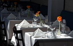 Restaurant White Cloth Tables. Afternoon light falls on white cloth tables set up and ready for action at a fine dinning restaurant in Austin, Texas Stock Photo