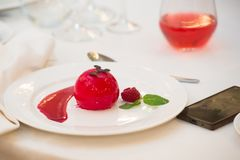 Ice cream sherbet in the form of a red ball stylized as an apple. In the restaurant on a white tablecloth ice cream in the form of a red ball. Stylization for stock image
