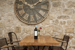 Restaurant. Wine bottle and two glasses on the wooden table decorated with rose Stock Images