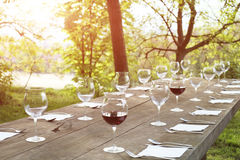 Restaurant wine glasses on a wooden table. Outdoor in the countryside Royalty Free Stock Image