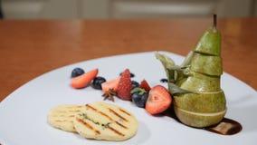 Restaurantconcept De witte plaat verfraaide met bessen en sneed peer Sluit van chef-kokhanden opzetten plakken van kaas stock footage