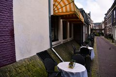 Restaurante acogedor en ladrillos cubiertos de musgo de la pared púrpura roja blanca amarilla del toldo de Amsterdam imagen de archivo