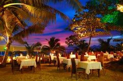 Restaurante al aire libre en la playa durante puesta del sol Foto de archivo libre de regalías