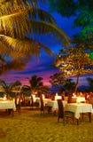 Restaurante al aire libre en la playa durante puesta del sol Imagen de archivo
