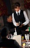Restaurante: Cena que ordena de la mujer del menú Foto de archivo