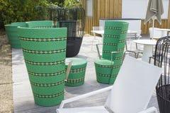 Restaurante con las sillas de mimbre verdes, las tablas y diversos colores de sillas Imagenes de archivo