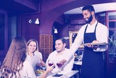 Restaurante de la clase media y camarero alegre imagen de archivo