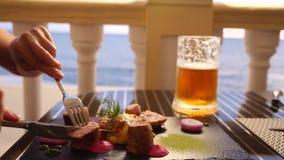 Restaurante do beira-mar Uma mulher come a carne e bebe a cerveja em um restaurante Movimento lento Close-up vídeos de arquivo