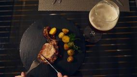 Restaurante do beira-mar Uma mulher come a carne e bebe a cerveja em um restaurante Movimento lento Close-up filme