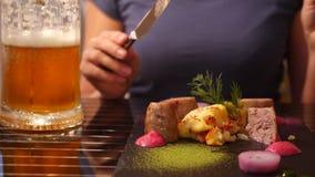 Restaurante do beira-mar Uma mulher come a carne e bebe a cerveja em um restaurante Movimento lento Close-up video estoque