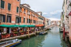Restaurante en el pequeño canal con los barcos en Venecia, Italia Fotos de archivo