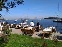 Restaurante exterior muito agradável com iate e opinião do mar imagem de stock