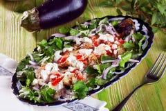 Restaurante guisado berenjena de la fuente de la cebolla del perejil de la placa de los tomates, aún vida en un acero de madera,  Foto de archivo