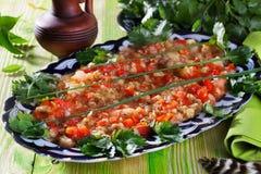 Restaurante guisado berenjena de la fuente de la cebolla del perejil de la placa de los tomates, aún vida en un acero de madera,  Imágenes de archivo libres de regalías