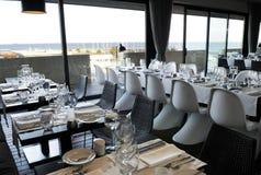 Restaurante moderno con vista al mar, servilletas blancas, sistema elegante de la tabla Imágenes de archivo libres de regalías