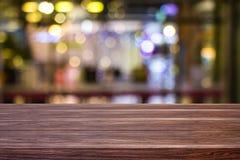 Restaurante ou cafetaria do café do borrão vazio da tabela de madeira escura com fundo abstrato borrado do bokeh claro do ouro pa imagens de stock royalty free
