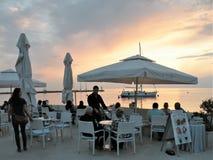 Restaurante por el mar con puesta del sol, gente en la cena, tablas debajo de los paraguas blancos fotografía de archivo