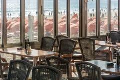 Restaurante vacío que pasa por alto una playa llena imagenes de archivo