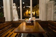 Restaurantinnenraum mit Holztischen und Blumen und Grünpflanzen stockbild