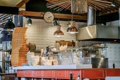 Restaurantküche mit einem enormen Stapel von Pizzakästen Lizenzfreies Stockbild