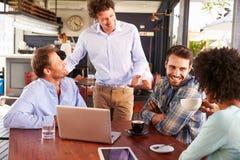 Restaurantmanager die aan klanten bij hun lijst spreken Royalty-vrije Stock Afbeelding