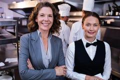 Restaurantmanager en serveerster die in commerciële keuken glimlachen stock fotografie