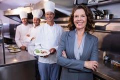 Restaurantmanager het stellen voor team van chef-koks Stock Afbeeldingen