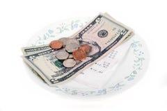 Restaurantrechnung mit Dollarscheinen (Tipps) auf einer Platte Lizenzfreie Stockfotografie