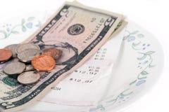 Restaurantrechnung mit Dollarscheinen (Tipps) auf einer Platte Stockbild
