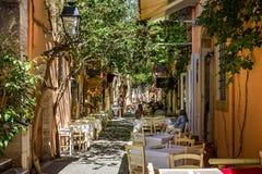 Restaurants, die Cafés in den im Freien in der schmalen Gasse unter geschecktem Sonnenlicht in Kreta, Griechenland sitzen stockbild