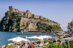 Restaurants on the sea in Ischia. Iaschia March 2017, Italy: Restaurants on the sea in Ischia Ponte with tourists who dine at the sight of the Aragonese Castle Royalty Free Stock Photography