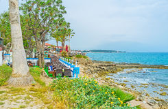 Restaurants on seashore of Side. The row of outdoor cafes and restaurants stretches along the rocky seashore of Side peninsula, Turkey Royalty Free Stock Photo