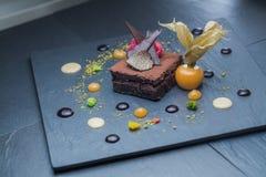 Restaurantschotel - de cake van de Browniechocolade met verse frambozen, zwarte truffel wordt verfraaid en carom, close-upfoto di Stock Foto