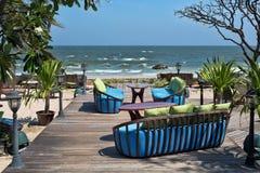 Restaurantstoelen en kussens tegen het overzees stock afbeeldingen