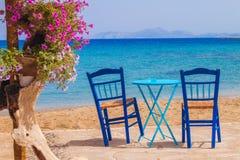 Restauranttabelle und -stühle mit einer entspannenden Ansicht von Moutsouna setzen, Naxos-Insel auf den Strand Stockfotos