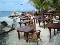 Restauranttabellen und -stühle im Sand Lizenzfreie Stockbilder