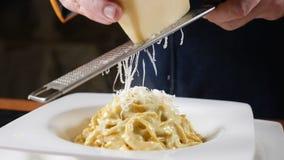 Restaurantvoedsel het koken Chef-kokgrating kaas op staalrasp die deegwaren met zeevruchten voorbereiden Langzame Motie Concept v stock footage