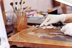 Restaurateur d'art travaillant sur l'icône antique Image libre de droits