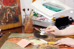 Restaurateur die aan het oude pictogram met bladgoud werken Royalty-vrije Stock Foto
