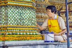 Restaurator som arbetar på en mosaique i Bangkok storslagna slott Arkivfoto