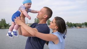 Reste d'été d'ajouter chanceux au bébé sur le lac, peu d'enfant dans des mains fortes du ` s de père près de la mère, clips vidéos