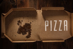 Reste der Pizza im Lieferungskasten mit Pizzazeit simsen Stockfotografie