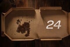 Reste der Pizza im Lieferungskasten mit 24 Zeittext Lizenzfreie Stockfotos