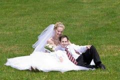 Reste des couples neuf-mariés sur l'herbe Photographie stock libre de droits